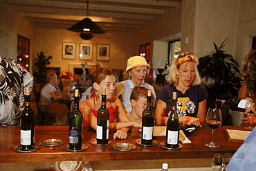 The whole family watches as the winetender makes a pour.