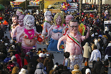 Masks and caricatures of politicians singing and dancing in the streets and enormous paper mache floats, surrounded by thousands of people, in the great celebration of the Carnival of Viareggio.