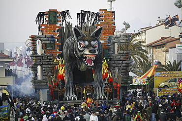Masks and caricatures of politicians singing and dancing in the streets and enormous paper machee floats, surrounded by thousands of people, in the great celebration of the Carnival of Viareggio.