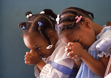 With heads bowed in silent prayer, two young African American girls show worship in a Liberty City, Florida church.