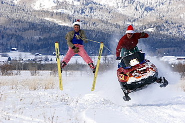 An excited man on a snowmobile gets some air while towing another man in pink snow pants on skis.