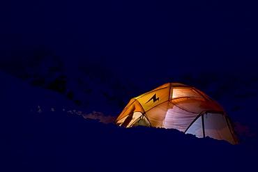 A base camp tent lit by lamp light at night, Brady Glacier, Glacier Bay National Park, Alaska.