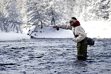 A fly fisherman standing in the river on a winter day.