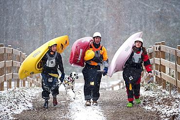 Three kayakers shoulder their kayaks in Tennessee.