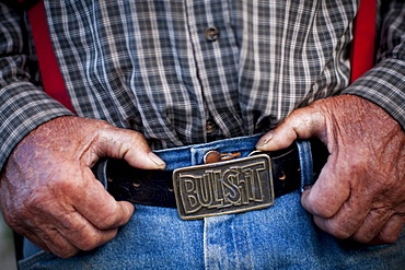 A rancher wears a belt buckle that reads