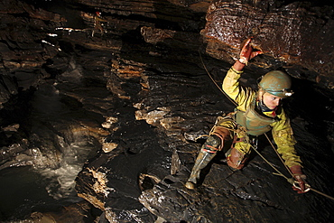 A young girl crawls on a ledge in a cave in China.