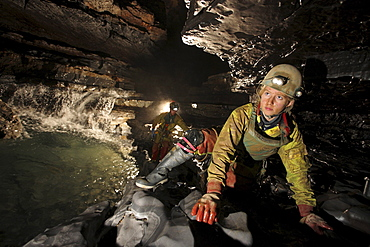 Two explorers crawl past along a ledge in a cave in China.