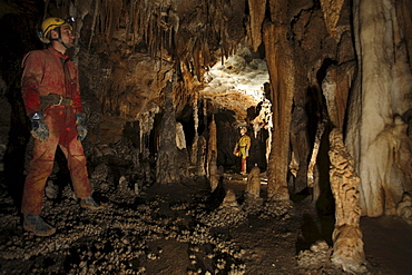 Cave explorers pose infront of cave formations underground in China.
