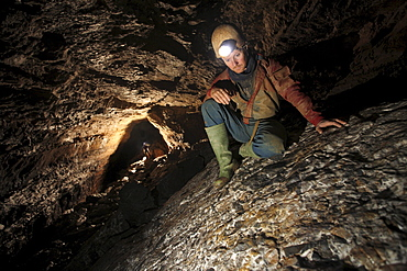 A man admires rock patterns underground in a cave in China.