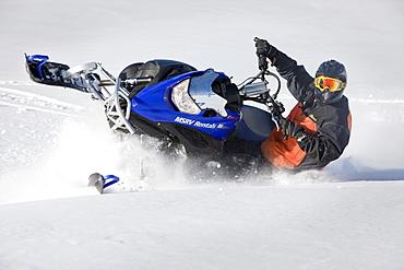 A man makes a sharp turn through powdery snow while snowmobiling on Owlshead Mountain.