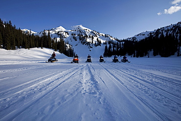 A line of six people on snowmobiles head toward the camera with Owlshead Mountain looming behind them.