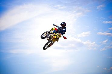 A motocross biker points towards the sky as he flies through a jump in Brainerd, Minnesota.