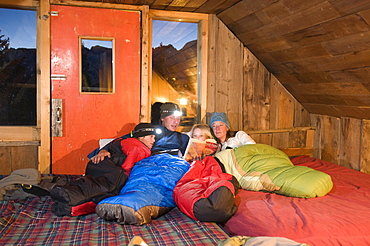 Family reading book in sleeping bags at the Saint Paul Lodge, San Juan National Forest, Colorado.
