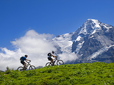 Two mountain bikers are riding through the grassy fields of the Murren plateau. In the background the famous Moench mountain.