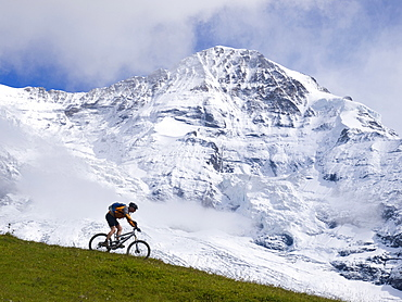 A Mountain biker is descending a grassy ridge in front of the Moench mountain (4099 meter).