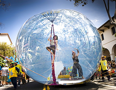 A young woman performs on ropes inside a giant inflatable float at a parade in Santa Barbara.