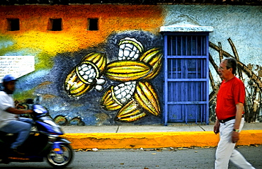 Men pass a street painting of cacao pods in Puerto Colombia, Venezuela.