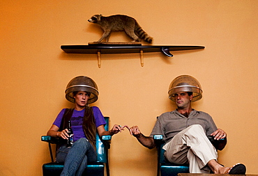 A portrait of a man and a woman with a raccoon above on the wall.