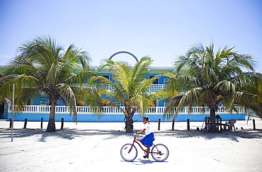 A little girl rides her bike on the sand in front of a colorful building and a row of palm trees.