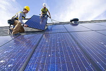 Two workers install solar panels on a rooftop in Redmond, WA.