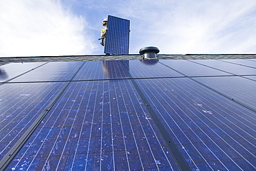 A worker installs solar panels on a rooftop in Redmond, WA.