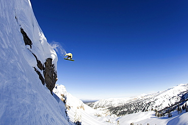 A male snowboarder rides off a 50 foot cliff in the Wyoming Backountry.