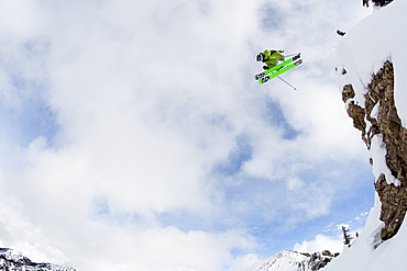 A male skier jumps off of a large cliff in the Wasatch backcountry, Utah.