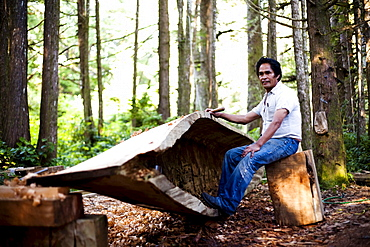 A man native to the West Coast of Vancouver Island carves a canoe as his tribes have for centuries.