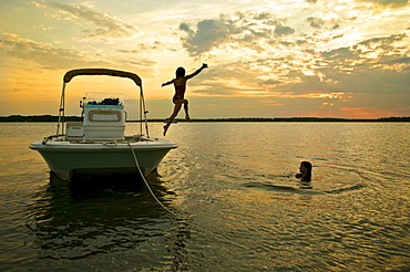 Children jumping off boat into water at sunset. McIntosh County, GA.