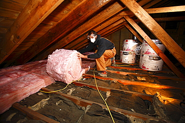 Man adds insulation to an attic