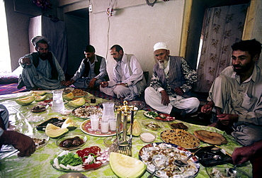 Afghan men and their guests eat a traditional feast of rice pilaf, mantu, and other dishes spread out on a plastic cloth, in an Afghan home in Mazar-i Sharif, Afghanistan