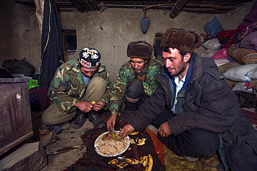 Kyrgyz and Wakhi men eat a simple meal of rice and bread in a mud hut at a winter camp in the Little Pamirs, Wakhan Corridor, Badakshan