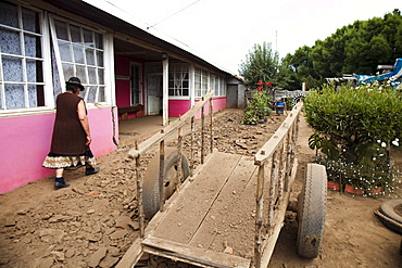 A local woman walks along a beaten dirt path next to a long building in Chile.