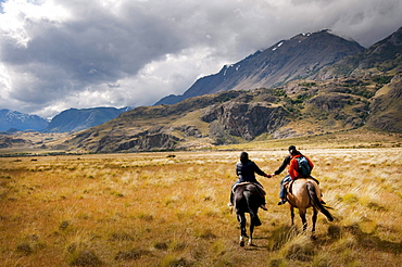 A monther and dayghter hold hands on horse back as they head off to herd sheep on Estancia Chacabuco, Patagonia.