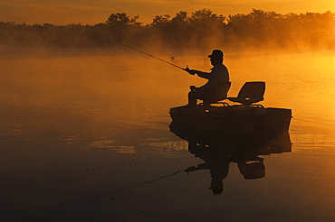 A man bass fishing on the lake at dawn with fog rising off of the lake in southern Illinois.