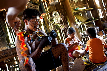 """Members of the Oro Win tribe make preparations and body decorations for an upcoming traditional """"festa"""" or celebration, Sao Luis Indian Post, Brazil."""