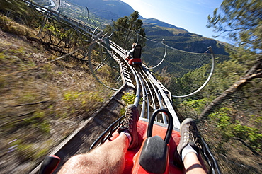 Two men ride the Alpine Coaster above Glenwood Springs at Glenwood Caverns Adventure Park, CO.