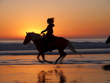 Riding a horse on the beach.