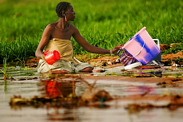 A Songhai woman kneeling in mud washing clothes in the Niger River, Gao, Mali, West Africa