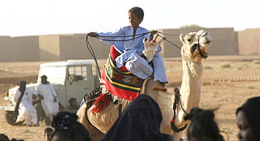 A Toureg child rides atop his camel, Gao, Mali, West Africa
