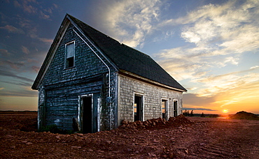 An old farm house sits partially buried as the sun sets in Prince Edward Island, Canada (HDR)