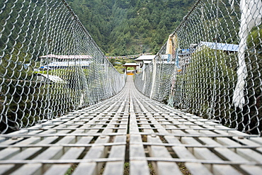 One of the many passageways across deep ravines and over rivers trekking in Nepal.  A suspension bridge made of aluminum, steel cables, and chain link fencing.