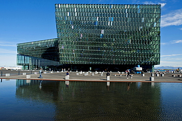People enjoying the grounds and reflecting pool around the concert hall/auditorium, Harpa (The Harp) in Reykjavik, Iceland.