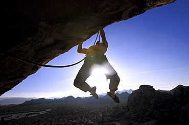 Justin Bastien climbing on an overhang in Joshua Tree National Park, California.