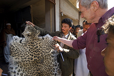 Wildlife biologist George Schaller examines a leopard skin being sold in the bazaar of Herat, Herat Province, Afghanistan.  Dr. George Schaller led a trip into the regions northwest of Herat to make a wildlife survey, looking especially for any signs of leopard, cheetah and wild ass.