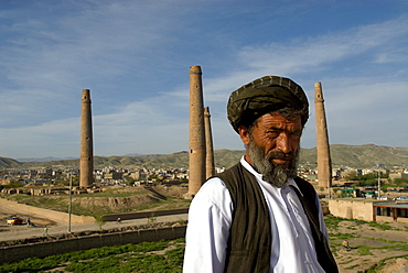 A guard at Queen Gawhar Shad's mausoleum, stands in front of four tall minarets, once part of a madrassa that was built in the 15th century by the last of the Timurid rulers, in Herat, Herat Province, Afghanistan.  One of the finest examples of Timurid architecture, the minarets are spectacular remnants of a much larger complex considered to be one of the finest examples of Timurid architecture