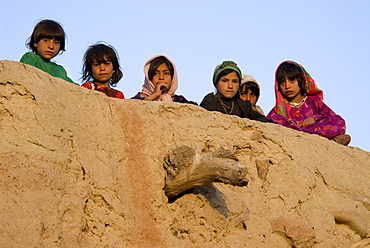 Young girls peer over the wall of a mud home in the Tajik village of Dera Jawal, at the base of the Band-e Baba range,  Herat Province, Afghanistan