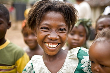 Young girl smiling. Gbolokai is a small town of a few hundred people 20 minutes off the main road near Totota, all of its inhabitants fled during the long brutal civil war and have slowly returned after 2005 to try and rebuild their lives.