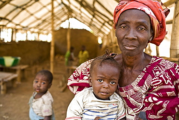 Elderly Liberian woman holds a crying baby in a day care center at a gravel pit on the  Voinjama - Foya road in Lofa County in Northern Liberia.