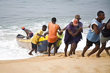 Group of young men pulling a fishing boat out of the ocean. Sulima is a fishing village on the Alantic coast at the mouth of the Moa River near the Liberian border.  Along its pristine beach, one of the longest in West Africa, fishermen launch dugout canoes and fish with nets drag back manually from the shore. Larger power boats mainly from Ghana leave from the more sheltered harbour on the Moa River. Most of the fish is smoke dried by the women of the village and then sold in markets as far off as Monrovia, Liberia.